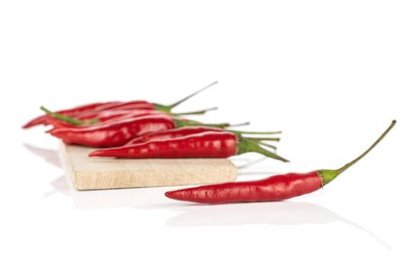 Lot of whole hot red chili on wooden cutting board isolated on white background