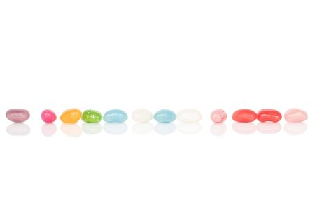 Lot of whole jelly bean candy in line isolated on white background Imagens
