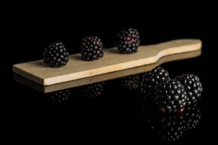 Group of six whole fresh black blackberry on small wooden cutting board isolated on black glass
