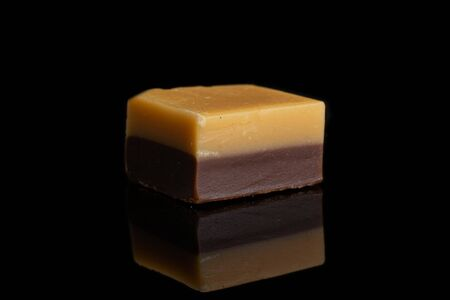 One whole sweet brown caramel chocolate candy isolated on black glass Imagens