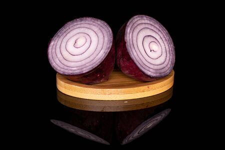 Group of two halves of tasty onion red on round bamboo coaster isolated on black glass Stock Photo