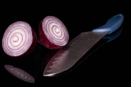 Group of two halves of tasty onion red with steel knife isolated on black glass