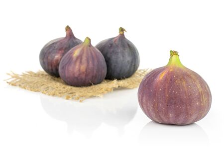 Group of four whole fresh purple fig on natural sackcloth isolated on white background