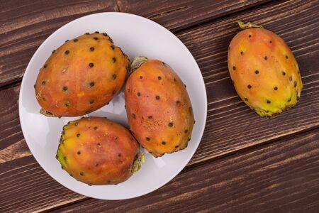 Group of four whole fresh orange opuntia on white ceramic plate flatlay on brown wood