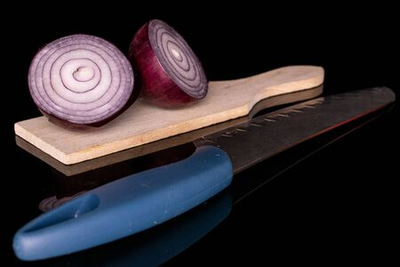 Group of two halves of tasty onion red on wooden cutting board with steel knife isolated on black glass Zdjęcie Seryjne