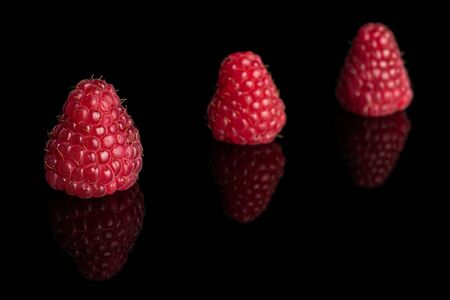Group of three whole fresh red raspberry isolated on black glass Stok Fotoğraf
