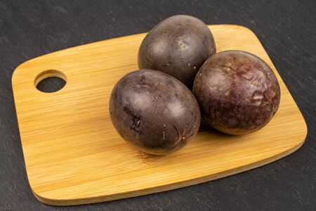 Group of three whole sweet dark purple passion fruit on bamboo cutting board on grey stone