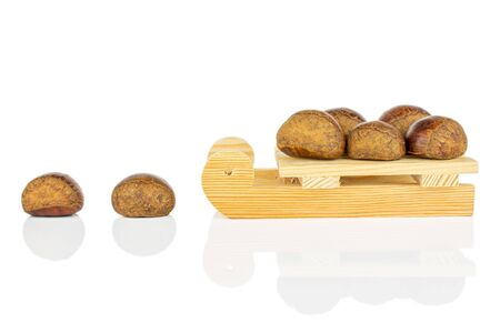 Group of seven whole sweet brown chestnut with wooden sledge isolated on white background