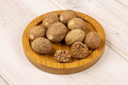 Group of eight whole one half one piece of dry brown nutmeg on bamboo coaster on white wood