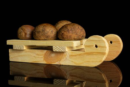 Group of four whole sweet brown chestnut with wooden sledge isolated on black glass