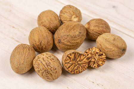Group of eight whole one half one piece of dry brown nutmeg on white wood Stok Fotoğraf