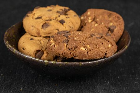 Group of four whole sweet brown cookie in glazed bowl flatlay on grey stone