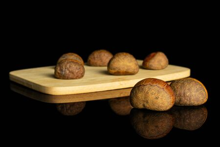 Group of seven whole sweet brown chestnut on bamboo cutting board isolated on black glass