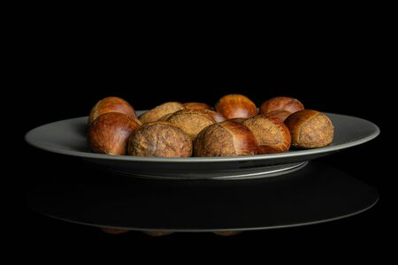 Lot of whole sweet brown chestnut on gray ceramic plate isolated on black glass Stok Fotoğraf