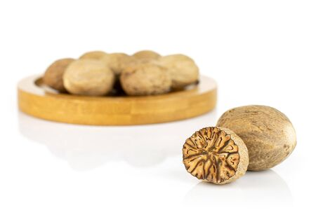 Lot of whole one half of dry brown nutmeg on bamboo coaster isolated on white background