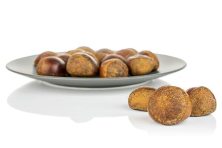 Lot of whole sweet brown chestnut on gray ceramic plate isolated on white background