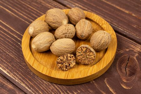 Group of eight whole one half one piece of dry brown nutmeg on bamboo coaster on brown wood