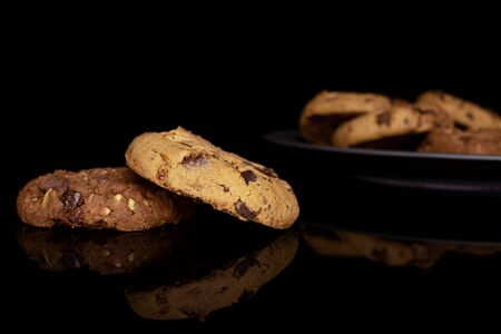 Group of six whole sweet brown cookie on gray ceramic plate isolated on black glass