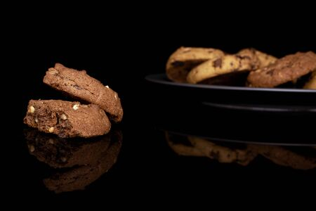 Lot of whole sweet brown cookie on gray ceramic plate isolated on black glass