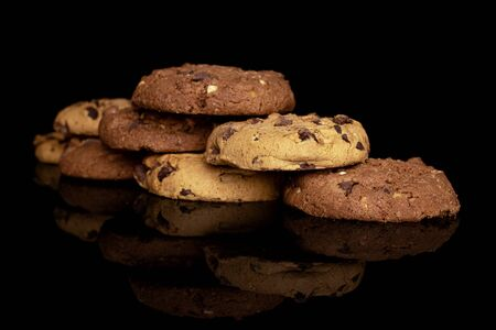 Group of eight whole sweet brown cookie isolated on black glass