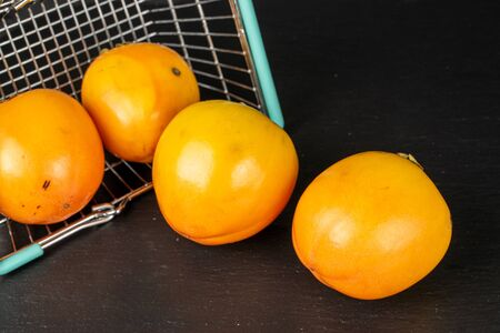 Group of four whole sweet orange persimmon in shopping basket on grey stone