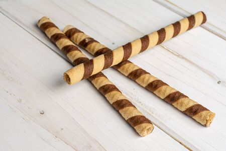 Group of three whole crunchy beige hazelnut rolled wafer biscuit on white wood 写真素材