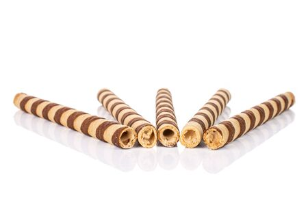 Group of five whole crunchy beige hazelnut rolled wafer biscuit in row isolated on white background