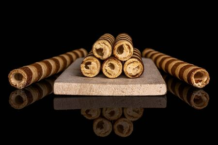 Group of seven whole crunchy beige hazelnut rolled wafer biscuit on small wooden cutting board isolated on black glass 写真素材