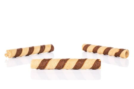 Group of three whole crunchy beige hazelnut rolled wafer biscuit one in front isolated on white background