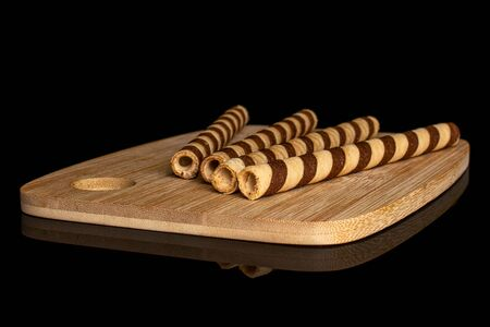 Group of four whole crunchy beige hazelnut rolled wafer biscuit on bamboo cutting board isolated on black glass