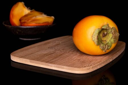 Group of one whole two halves of sweet orange persimmon in glazed bowl on bamboo cutting board isolated on black glass