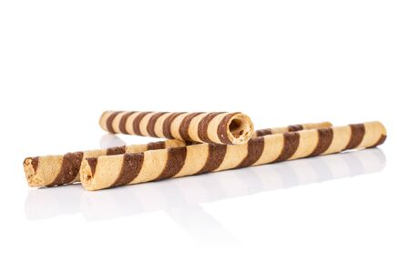 Group of three whole crunchy beige hazelnut rolled wafer biscuit isolated on white background