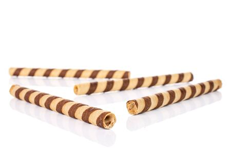 Group of four whole crunchy beige hazelnut rolled wafer biscuit isolated on white background