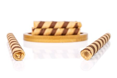Group of seven whole crunchy beige hazelnut rolled wafer biscuit on bamboo coaster isolated on white background