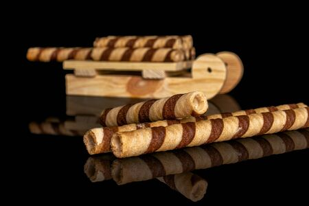 Group of eight whole crunchy beige hazelnut rolled wafer biscuit with wooden sledge isolated on black glass