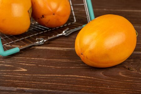 Group of three whole sweet orange persimmon in shopping basket on brown wood Banco de Imagens