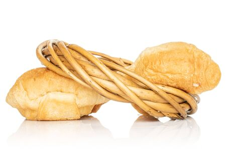 Group of two whole fresh baked mini croissant in wicker vine circle isolated on white background