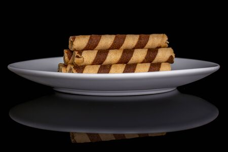 Group of six whole crunchy beige hazelnut rolled wafer biscuit on white ceramic plate isolated on black glass