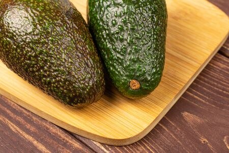 Group of two whole fresh green avocado on bamboo cutting board on brown wood
