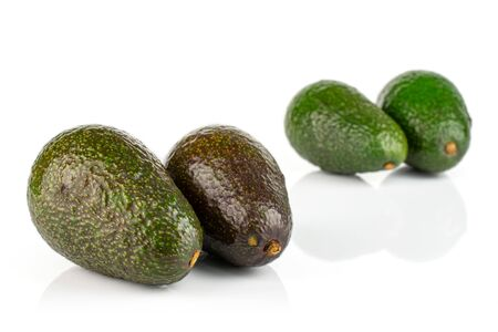 Group of four whole fresh green avocado placed in two groups isolated on white background