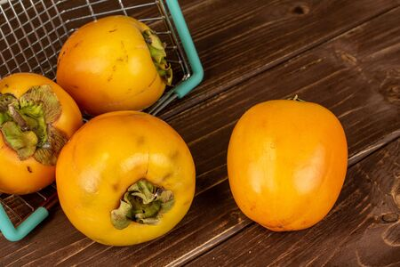 Group of four whole sweet orange persimmon in shopping basket on brown wood Banco de Imagens
