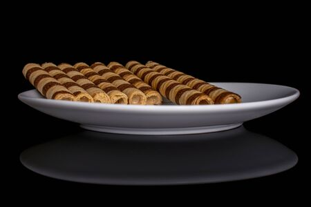 Group of eight whole crunchy beige hazelnut rolled wafer biscuit on white ceramic plate isolated on black glass