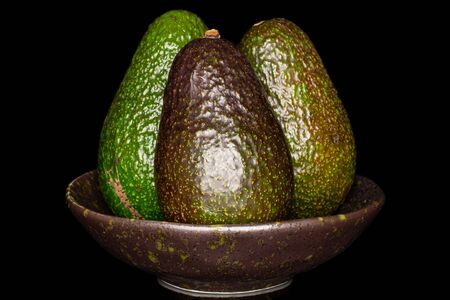 Group of three whole fresh green avocado in dark ceramic bowl isolated on black glass