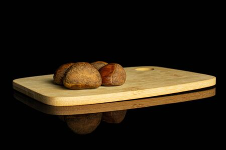 Group of four whole sweet brown chestnut on bamboo cutting board isolated on black glass