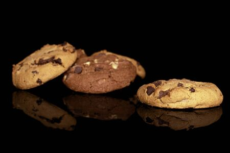 Group of three whole sweet brown cookie isolated on black glass Stock Photo