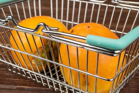 Group of two whole sweet orange persimmon in shopping basket on brown wood
