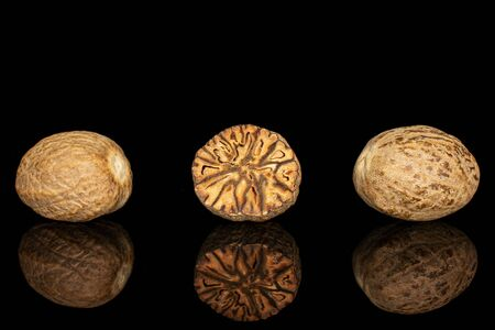 Group of two whole one half of dry brown nutmeg isolated on black glass