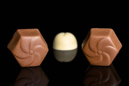 Group of three whole delicious chocolate praline placed symmetrically isolated on black glass Stock Photo