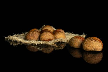 Group of nine whole sweet brown chestnut on natural sackcloth isolated on black glass