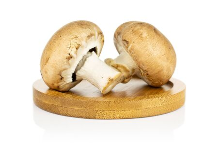 Group of two whole fresh brown champignon on bamboo coaster isolated on white background Stock Photo